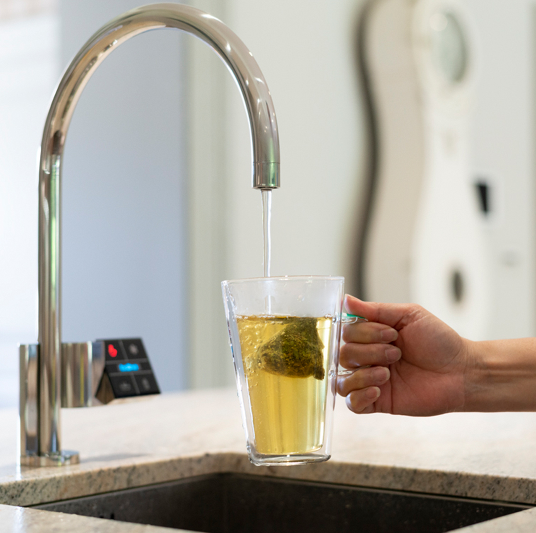 Quatreau tap in polished stainless steel finish dispenses boiling water into glass mug of herbal tea